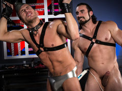 Athletic Alexander Gustavo's wrist restraints are tied to a spreader cane hanging above his head. Beefcake Jaxton Wheeler, covered in a full rubber uniform, spanks Alexander's ass, leaving his ass cheeks with a pink tinge. Grabbing an anal massager, Jaxto